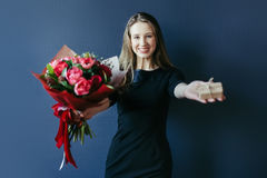 Cute girl with bouquet of red tulips and surprise woodenbox. Royalty Free Stock Images