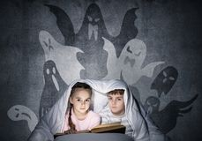 Cute girl and boy reading book in bed royalty free stock images