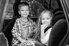 Cute girl and boy sitting in car royalty free stock image