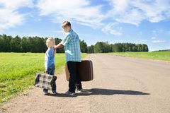Cute girl and boy with suitcase. On road Royalty Free Stock Photo