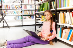 Cute girl with braid holds laptop in library Royalty Free Stock Images