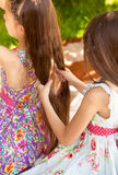Cute girl braiding elder sister at park Royalty Free Stock Image