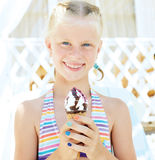 Cute girl in the bright bathing suit eating a delicious ice cr Royalty Free Stock Photography