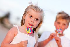 Cute Girl and Brother Enjoying Their Lollipops Royalty Free Stock Photos