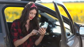 Cute girl browsing the net with smartphone in car stock video