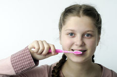 Cute girl brushing teeth on white Royalty Free Stock Photos