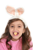Cute girl with bunny ears. Holds a candy heart in between her teeth that reads sweet hearts Stock Image