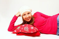 Cute girl with a cap and a pillow lying  on white backgr Royalty Free Stock Photo