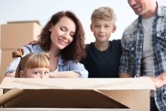 Cute girl in cardboard box and her family indoors. Moving into new house royalty free stock photo