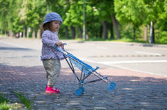 Cute girl with the carriage in the park Royalty Free Stock Photo