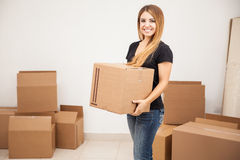 Cute girl carrying some boxes. Beautiful young woman carrying some boxes and moving to her new place stock photos