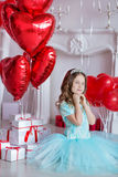 Cute girl celebrating birth day together close to red balloons.Lovely scene of girl in blue dress. Stock Image