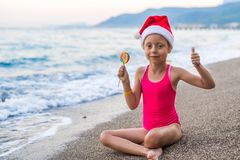 Cute girl celebrating New Year and Christmas on the beach in a hat of Santa Claus, free space. Christmas background, winter holidays in tropical countries stock images