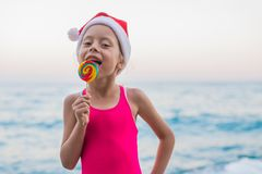 Cute girl celebrating New Year and Christmas on the beach in a hat of Santa Claus, free space. Christmas background, winter holidays in tropical countries royalty free stock images