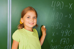 Cute girl with chalk in hand near blackboard Royalty Free Stock Photo