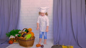 Cute girl chef collecting vegetables into basket. stock footage