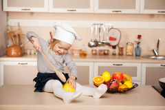 Cute girl with chef hat holding big wooden spoon Royalty Free Stock Photography