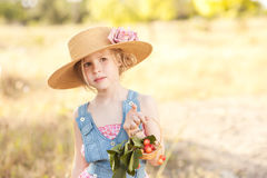 Cute girl with cherries. Cute kid girl holding basket with cherries outdoors Royalty Free Stock Images