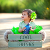 Cute girl child sitting in box with bottle of water Royalty Free Stock Photos