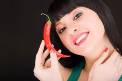 Cute girl with chili pepper. On the black background royalty free stock photos