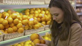 Cute girl chooses fresh citrus fruits in the supermarket. And fooling around stock video footage