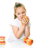 Cute girl choosing between apples and cake Stock Image