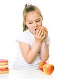 Cute girl choosing between apples and cake Stock Image