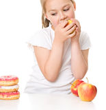 Cute girl choosing between apples and cake Stock Photos