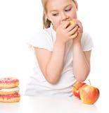 Cute girl choosing between apples and cake Stock Photos
