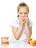 Cute girl choosing between apples and cake Royalty Free Stock Photography
