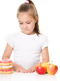 Cute girl choosing between apples and cake Royalty Free Stock Images