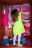 A cute girl choosing dress. A cute child choosing dress in her wardrobe Royalty Free Stock Image