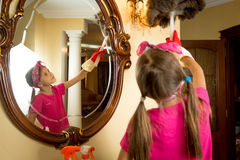 Cute girl cleaning mirror and lamp with brush Stock Images