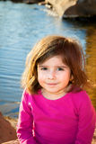 Cute Girl Closed Mouth Smile. A cute little girl sits slouching by a pond on a sunny day Royalty Free Stock Photo