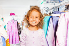 Cute girl among clothes on the hanger in  shop Stock Photos