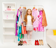 Cute girl among colorful bright dresses, clothes. And woman shoes on the floor during shopping stock photo