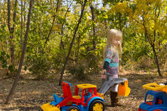 Cute girl with colorful construction vehicles Stock Images