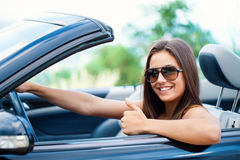 Cute girl in convertible doing thumbs up. Royalty Free Stock Photography