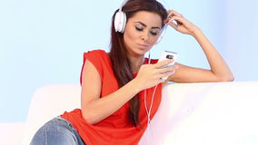 Cute girl on couch listen to the music Stock Photography