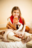 Cute girl covered in blanket drinking hot tea with lemon in bed Royalty Free Stock Photos
