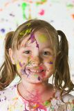 Cute girl covered in paint. A cute young girl covered in splattered paint Stock Photography