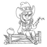 Cute girl in a cowboy costume sits on a fence Royalty Free Stock Image