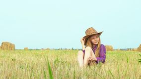 Cute girl in cowboy hat posing at photo session on rural field with haystack. Teenager girl in cowgirl look posing for. Camera on haystack background at stock footage
