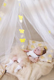 Cute girl in cream crib and canopy Stock Photo