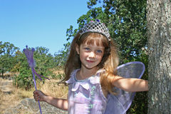 Cute girl with crown and wings. Cute young girl with crown, magic wand and butterfly wings in countryside Stock Photos
