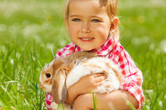 Cute girl cuddling rabbit in green field Royalty Free Stock Image