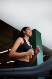 Cute girl with curly hair running on a treadmill in a modern gym light Royalty Free Stock Image