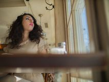 Cute girl with curly hair sits at a table in a cafe and looks out the window royalty free stock photography