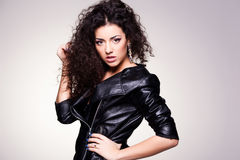 Cute girl with curly hair wearing a leather jacket - studio shot Royalty Free Stock Photos