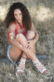 Cute girl with curly hairs sitting on the dry grass Stock Photo